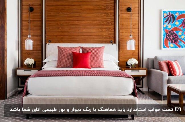 دکوراسین اتاق خوابی با تخت استاندارد و دو چراغ آویز اطراف تخت مقابل دیوار چوبی