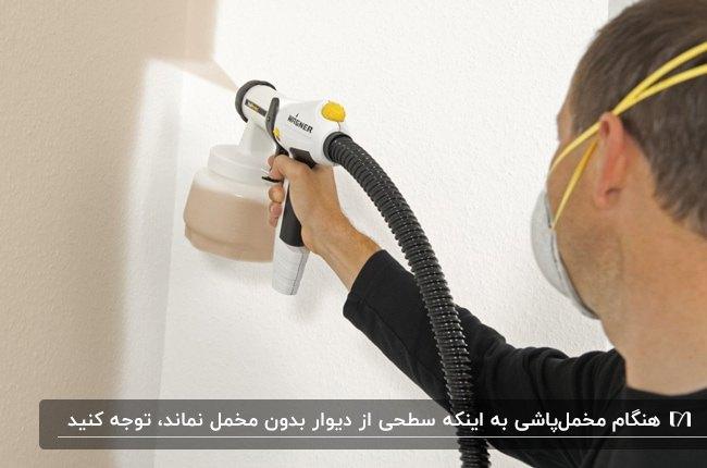 تصویر مردی در حال اجرای تکنیک مخمل پاشی کرم رنگ روی دیوار سفید