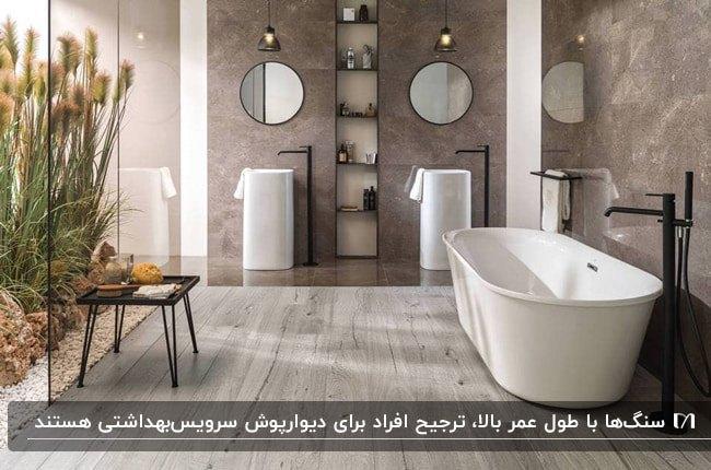 سرویس بهداشتی بزرگی با دیوارپوش سنگی قهوه ای، دو روشویی استوانه سفید و دو آینه گرد