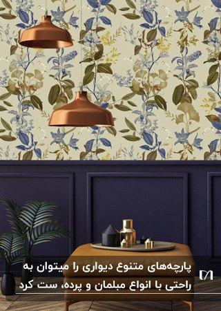 میز مربعی قهوه ای، دو چراغ آویز مسی و پارچه دیواری با طرح های سبز و آبی