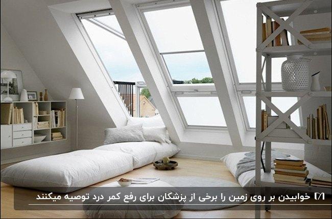 اتاق خواب زیرشیروانی با پنجره های بزرگ، قفسه کتاب و آباژور و رخت خواب سفید زیر پنجره