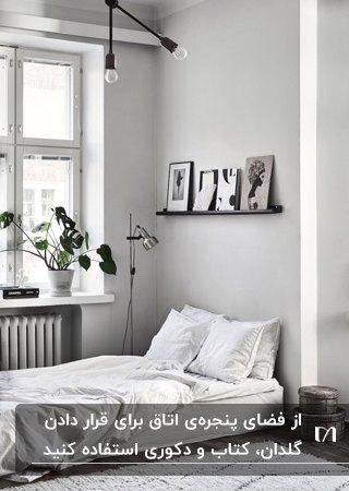اتاق خواب طوسی و سفید مشکی رنگی با محل خواب زیر پنجره ای با قفسه سفید که گلدان و کتاب روی آن است