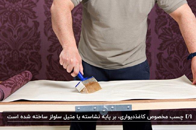 تصویر مردی در حال زدن چسب پشت کاغذدیواری های طرحدار بنفش رنگ