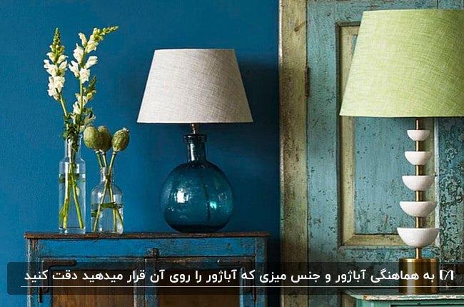 تصویر فضای آبی رنگ خانه ای با دو مدل متفاوت آبژور رومیزی یکی شیشه ای و دیگری سنگی و فلزی