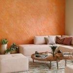 نشیمنی با مبل ال شکل و پاف کرم رنگ و دیوار مخمل پاشی شده نارنجی