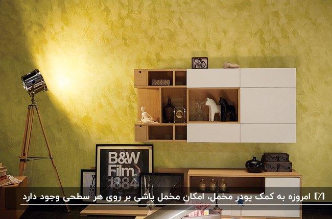 تصویر اتاقی با دیوار زرد و تکنیک مخمل پاشی، قفسه چوبی روی دیوار و آباژور پایه بلند