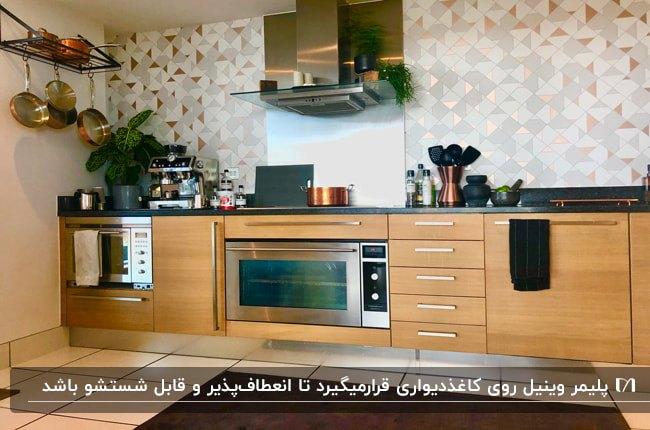 آشپزخانه ای با کابینت های چوبی و هود استیل با کاغذدیواری طرحدار وینیل