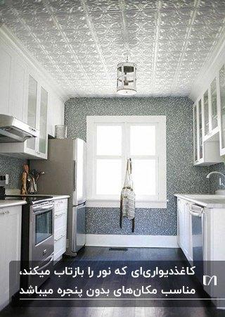 تصویر آشپزخانه طوسی رنگی با کابینت های سفید و کاغذدیواری طرحدار و براق سقف برای بازتاب نور