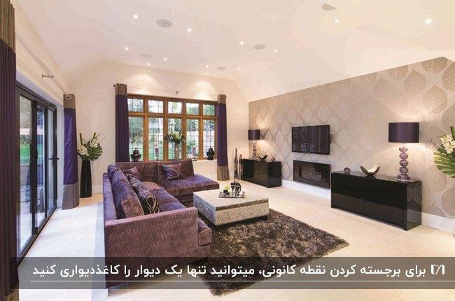 نشیمنی با دیوارهای سفید و یک دیوار با کاغذدیواری طرحدار و مبلمان ال شکل بنفش مخمل