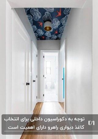 راهرویی با دیوارهای سفید، درهای اتاق خواب سفید و کاغذدیواری با طرح های آبی و قرمز روی سقف