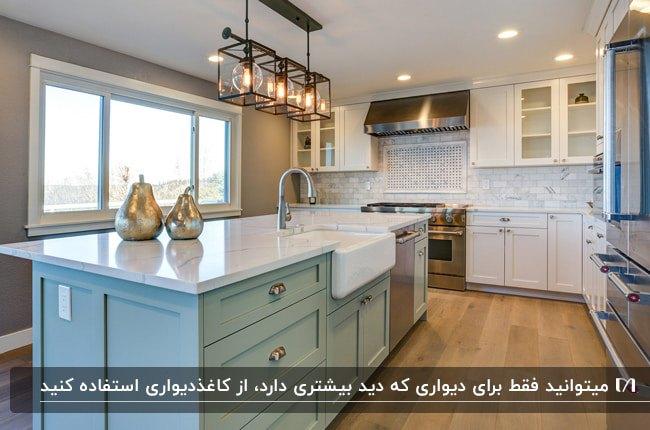 آشپزخانه ای با کابینت های سفید و جزیره سبز پاستلی و کاغذدیواری سفید طرحدار برای یک دیوار
