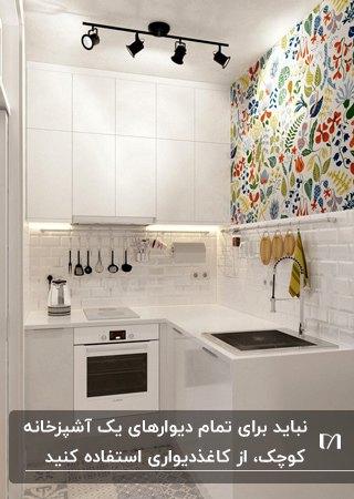 آشپزخانه کوچکی با کابینت های سفید و کاغذدیواری گلدار رنگی برای قسمتی از دیوار