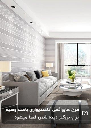 نشیمنی با مبل طوسی و کوسن های طوسی و زغالی و زرد به همراه کاغذدیواری با طرح های افقی طوسی و سفید