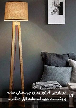 نشیمنی با تم رنگی طوسی و خاکستری و یک آباژور پایه بلند چوبی