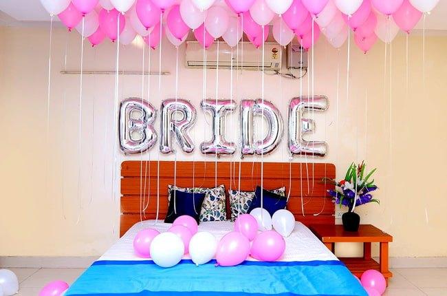 تصویر یک اتاق تزئین شده برای عروس و داماد با بادکنک های صورتی و سفید روی تخت چوبی