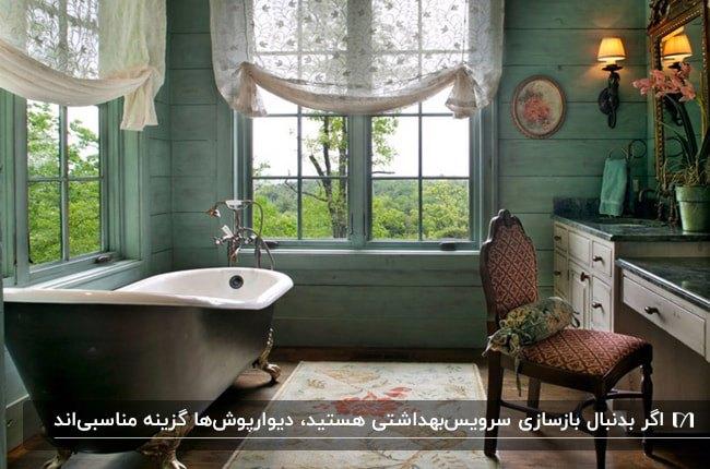 سرویس بهداشتی به سبک روستایی با دو پنجره، دیوارپوش سبز و صندلی چوبی با روکش قرمز و کرم