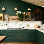 آشپزخانه ای با کابینت های سبز تیره و کاغذدیواری سفید بین کابینتی با طرح سنگ مرمر