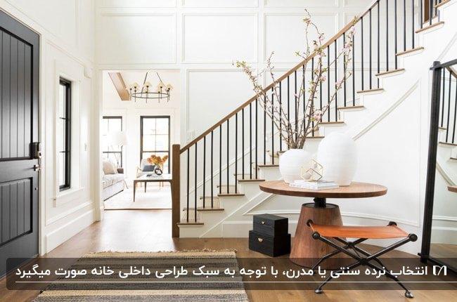 ورودی خانه ای مدرن با راه پله چوبی، میز گرد چوبی و گلدان های سفید روی میز