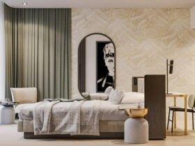 اتاق خوابی با تخت خواب و میز کار ست وسط اتاق، آینه بیضی روی دیوار و کاغذدیواری طرحدار