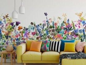 نشیمنی با مبل ال شکل فسفری و کوسن های رنگی مقابل دیواری با کاغذدیواری گل دار رنگارنگ