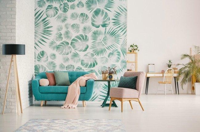 نشیمنی با مبل سبزآبی و تک نفره صورتی، کوسن های رنگی و پارچه دیواری سفید با طرح برگ های سبز