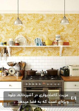 آشپزخانه ای با کابینت سفید، صفحه رو کابینتی چوبی و کاغذدیواری زرد با طرح های سفید