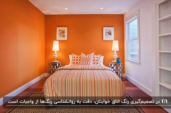 اتاق خوابی با دیوارهای نارنجی، روتختی طرحدار نارنجی و دو چراغ دیوارکوب اطراف تخت