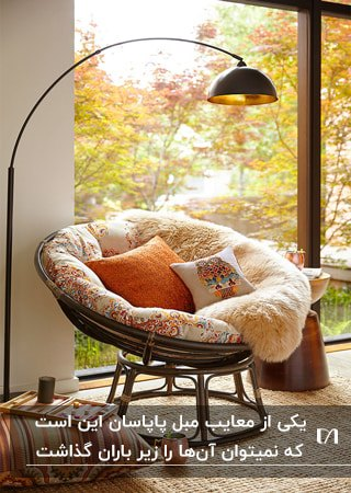پاپاسانی قهوه ای با کوسن نارنجی کنار دیوار شیشه ای و آباژور مشکی پایه بلند