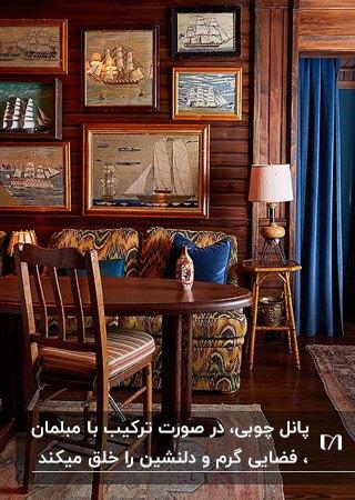 اتاق غذاخوری با دیوار چوبی، میز و صندلی های چوبی و مبل طرحدار با کوسن های آبی