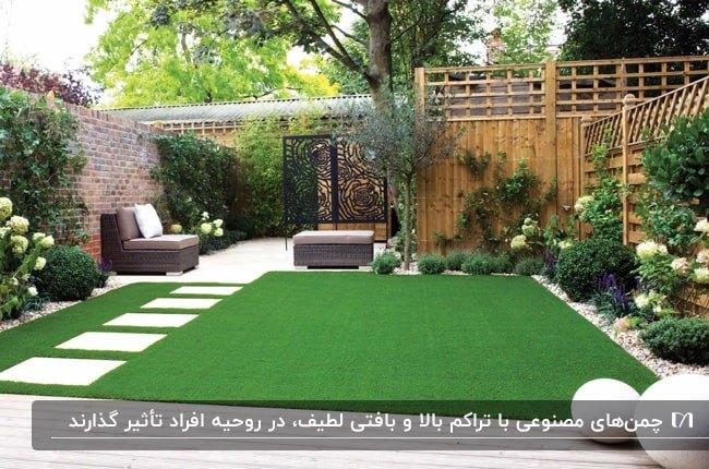 حیاطی با کفپوش چمن مصنوعی، باغچه و گل ها و گیاهان و مبل راحتی