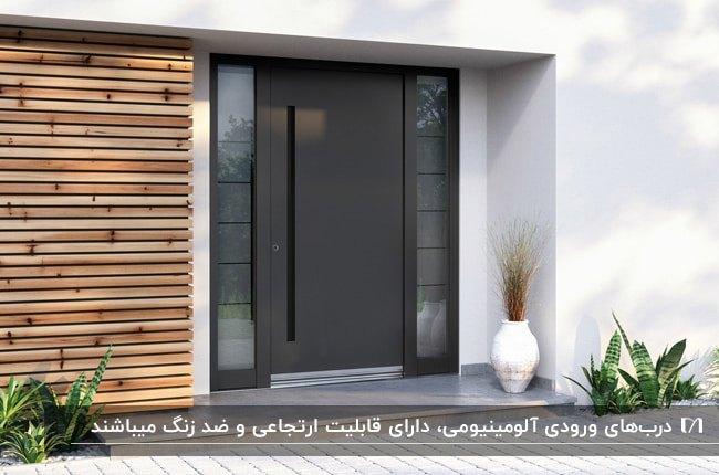 تصویر ورودی خانه ای با دیوارپوش چوبی و درب آلومینیومی مشکی مات