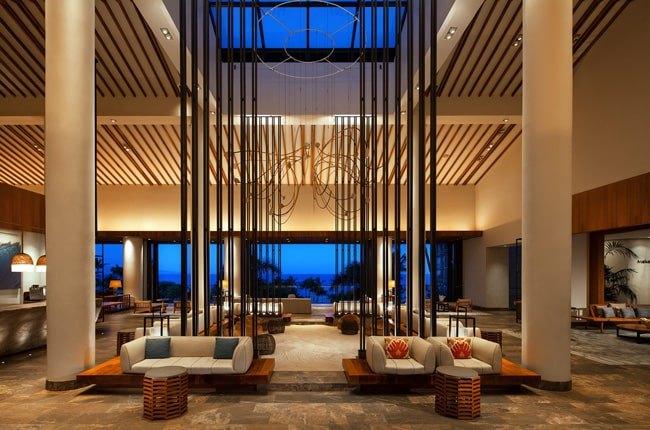 لابی هتل مجللی با سقف شیشه ای و ویوی شیشه ای یک دیوار و مبلمان کرم رنگ