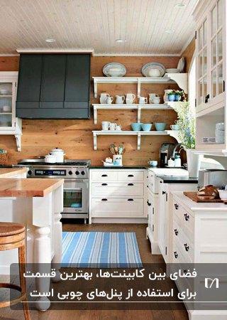 آشپزخانه ای با کابینت های سفید، دیوار چوبی بین کابینت ها و هود مشکی