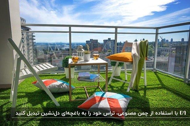 تراس کوچکی با حفاظ شیشه ای، کفپوش چمن مصنوعی و میز و صندلی های سفید