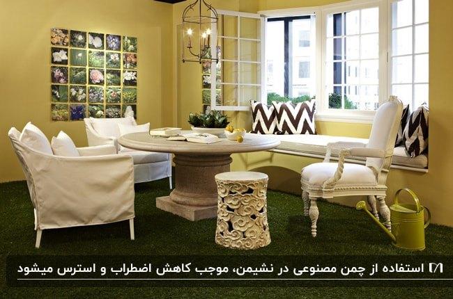 اتاق پذیرایی با میز گرد و مبلمان سفید، کفپوش چمن مصنوعی و دیوارهای سبز کمرنگ