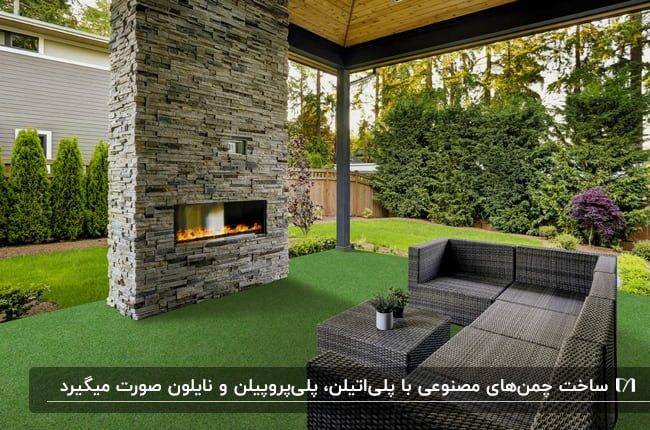 ایوانی با مبل خاکستری ال شکل، شومینه با دیوار سنگی و کفپوش چمن مصنوعی