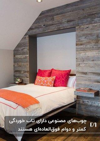 اتاق خوابی با تخت تاشو، روتختی سفید با بالشت های سرخابی و دیوار چوبی خاکستری