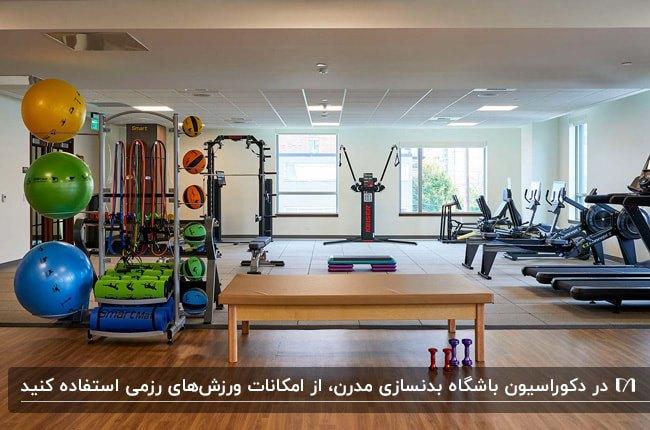 دکوراسیون یک باشگاه بدنسازی با کفپوش چوبی و بخش های برای ورزش های رزمی