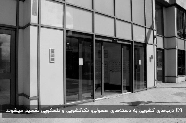 تصویر نمای خارجی ورودی یک ساختمان نقره ای و خاکستری با درب شیشه ای اتوماتیک کشویی