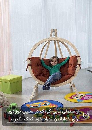 تصویر اتاق خواب کودک با یک صندلی تابی گرد پایه دار چوبی با تشکچه آجری