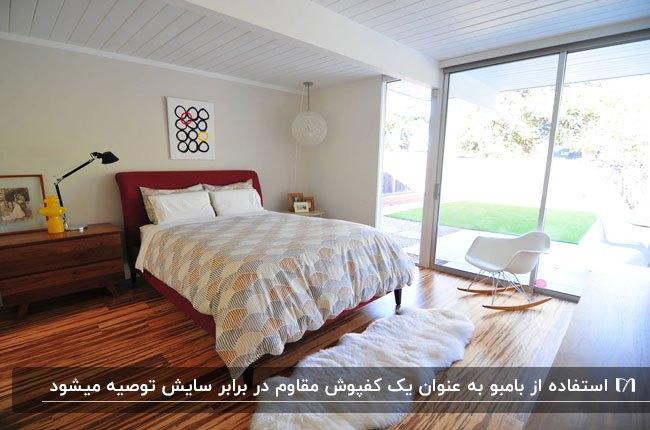 اتاق خوابی با کفپوش مقرون به صرفه بامبو، تخت، صندلی سفید و خز سفید زیر تخت
