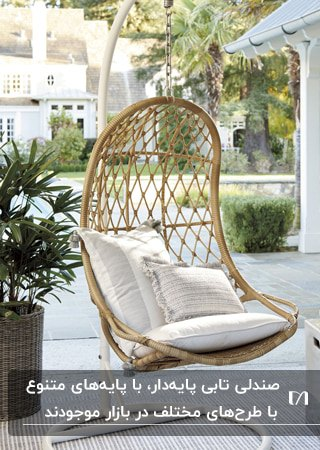 تصویر یک صندلی تابی حصیری به رنگ چوب با تشکچه و دو کوسن سفید در فضای باز