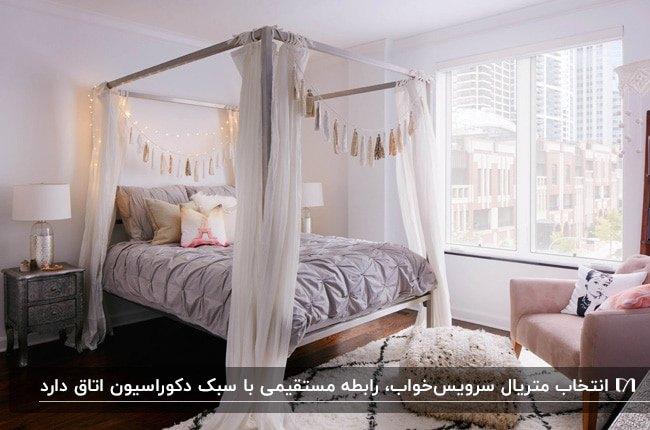 اتاق خوابی با تخت خواب پرده دار چوبی با پرده های حریر سفید و ریسه های طلایی کنار صندلی صورتی
