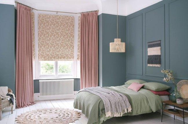 اتاق خوابی با دیوارهای فیلی رنگ، پرده های صورتی و روتختی سبز رنگ
