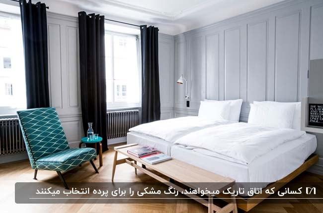 اتاق خوابی با دو تخت تک نفره کنار هم و پرده های مشکی با مبل آبی