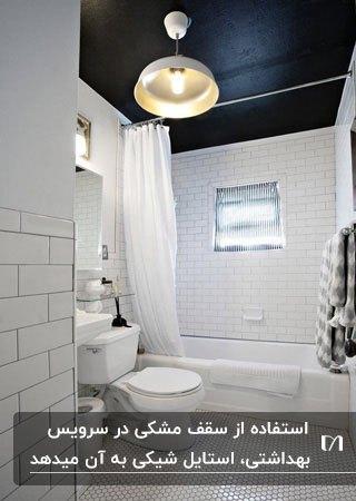 سرویس بهداشتی کوچک و سفید رنگی با سقف مشکی و لوستر آویز گرد فلزی