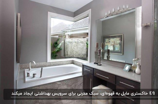 سرویس بهداشتی با دیوارهای طوسی مایل به قهوه ای، وان سفید با پنجره کنج دیوار