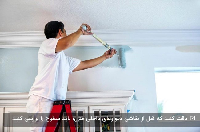 مردی در حال زدن رنگ آبی آسمانی با غلتک روی دیوارهای سفید رنگ