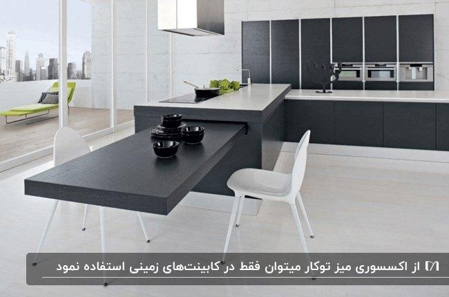 آشپزخانه ای با کابینت و جزیره مشکی رنگ و اکسسوری میز توکار مشکی با صندلی سفید