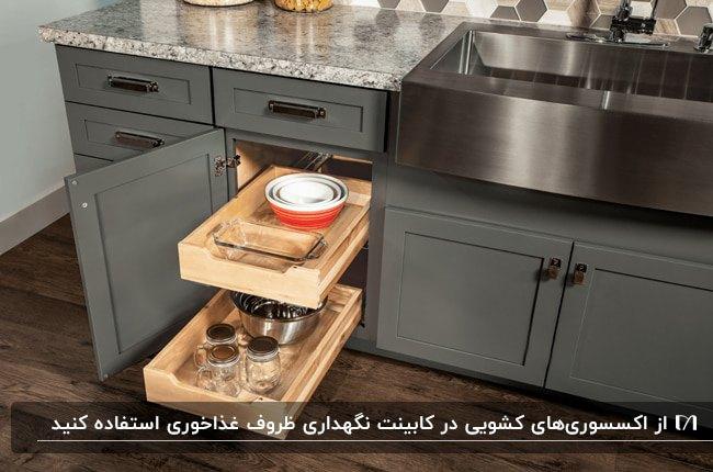 آشپزخانه ای با کابینت های خاکستری و اکسسوری های کشویی چوبی